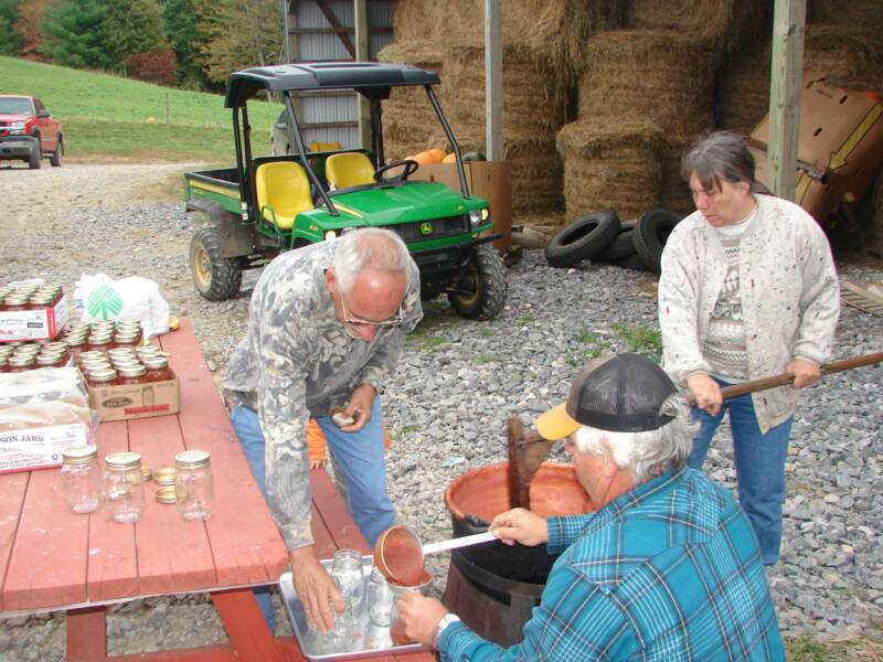 Ronald, Jennifer's Mom, and Dad putting apple butter in jars