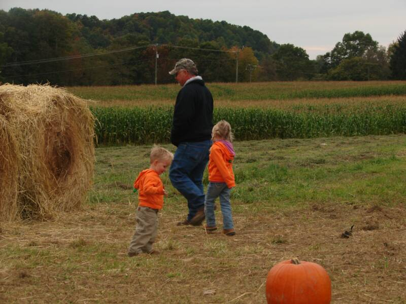 "Austin and Abby playing with ""Uncle Dewey"" in the hay tunnel"